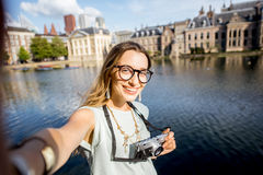 Woman in Haag, Netherlands. Portrait of a young woman tourist with photo camera in the centre of Haag city in Netherlands Royalty Free Stock Photos