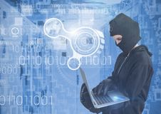 Woman hacker with hood using a laptop in data center Stock Image