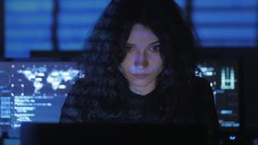 Woman Hacker programmer with curly hair is working on computer in cyber security center filled with display screens. Female Hacker programmer is working on stock footage
