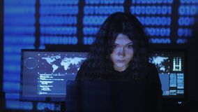 Woman hacker programmer with curly hair is working on computer in cyber security center filled with display screens. Female hacker programmer is working on stock video footage