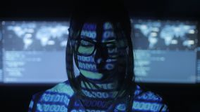 Woman Hacker programmer in glasses is working on computer in cyber security center filled with display screens. Binary. Female Hacker programmer in glasses is stock video footage