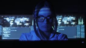 Woman Hacker programmer in glasses is working on computer in cyber security center filled with display screens. Binary. Female Hacker programmer in glasses is stock footage