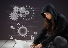 Woman hacker using a laptop in front of purple background with digital icons Royalty Free Stock Photos