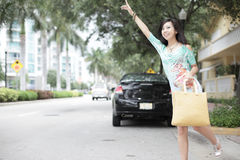 Woman hailing a cab. Young Asian woman hailing a taxi cab in the city Royalty Free Stock Photos
