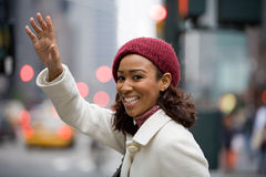 Woman Hailing a Cab. A pretty young business woman hails a taxi cab in the city Royalty Free Stock Photography