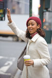 Woman Hailing A Cab. A pretty young business woman hails a taxi cab in the city Royalty Free Stock Image