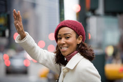 Woman Hailing A Cab. A pretty young business woman hails a taxi cab in the city Stock Photography