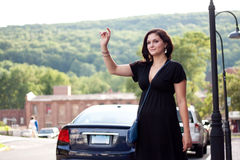 Woman Hailing a Taxi Cab. A beautiful brunette woman waving her arm tries to hail a cab at the side of the road in the city Stock Image