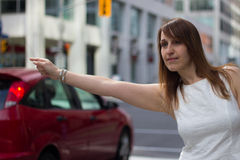 Woman hails a taxi on a downtown street Stock Photography