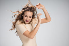 The woman with hair blowing in the wind on gray Stock Photos