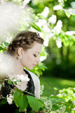 Woman with a hair braid in a blossoming park. Royalty Free Stock Photos