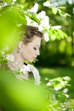 Woman with a hair braid in a blossoming park. Royalty Free Stock Photography