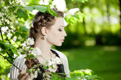 Woman with a hair braid in a blossoming park. Royalty Free Stock Photo
