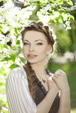 Woman with a hair braid in a blossoming park. Royalty Free Stock Images