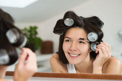 Woman in hair curlers applying eye makeup Royalty Free Stock Image