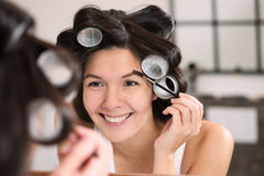 Woman in hair curlers applying eye makeup Stock Photography
