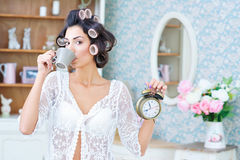 Woman in hair curlers with coffee and clock in the morning. Morning rush. Beautiful woman in hair curlers drinking coffee and holding a clock in her hand Stock Photo