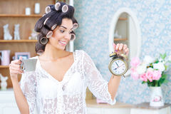 Woman in hair curlers with coffee and clock in the morning. Morning rush. Beautiful woman in hair curlers holding cup of coffee and looking at the clock Royalty Free Stock Image