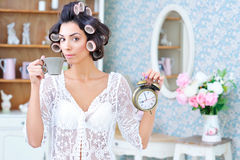 Woman in hair curlers with coffee and clock in the morning. Morning rush. Beautiful woman in hair curlers holding cup of coffee in one hand and a clock in the Royalty Free Stock Image
