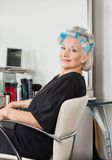 Woman With Hair Curlers Sitting On Chair At Salon Royalty Free Stock Photos