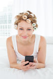 Woman in hair curlers text messaging in bed Royalty Free Stock Photo