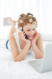 Woman in hair curlers using cellphone and laptop in bed Royalty Free Stock Image