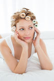 Woman in hair curlers using cellphone while lying in bed Stock Image