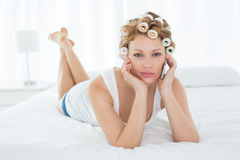 Woman in hair curlers using cellphone while lying in bed Royalty Free Stock Photos