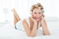 Woman in hair curlers using cellphone while lying in bed Royalty Free Stock Photography