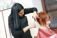 Woman hair cutting work. Stylist cutting hair of a female client at the beauty salon Stock Images