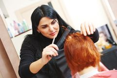 Woman hair cutting work. Stylist cutting hair of a female client at the beauty salon Royalty Free Stock Images