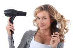 Woman with hair dryer. Blond woman with a hair dryer stock images