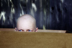 Woman with hair loss from chemotherapy peeks out from box Stock Photography
