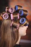 Woman with hair roller on hair Stock Photos