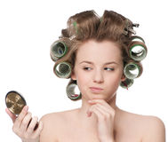 Woman in hair roller looking in mirror Royalty Free Stock Images