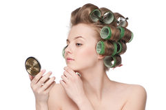 Woman in hair roller looking in mirror Stock Image