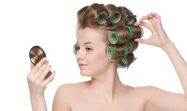 Woman in hair roller looking in mirror Royalty Free Stock Image