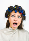 Woman with hair rollers. In her hair Royalty Free Stock Photos