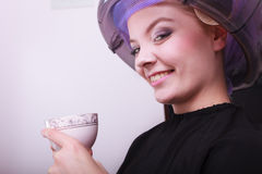 Woman hair rollers curlers drinking coffee tea hairdryer beauty salon Stock Photography