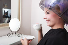Woman hair rollers curlers drinking coffee tea hairdryer beauty salon. Young woman female client drinking hot drink coffee tea in hairdressing beauty salon. Girl Stock Photo