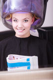 Woman hair rollers curlers reading magazine hairdryer beauty salon Royalty Free Stock Photo