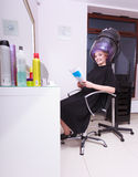 Woman hair rollers curlers reading magazine hairdryer beauty salon Stock Photos