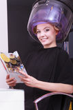 Woman hair rollers curlers reading magazine hairdryer beauty salon. Young woman female client reading magazine in hairdressing beauty salon. Girl in hair rollers Stock Photography
