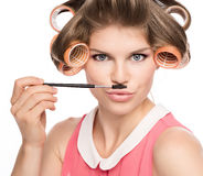 Woman in hair rollers. Funny picture of beautiful female in curlers with mustache, isolated on white. Cute Caucasian woman in studio Royalty Free Stock Image