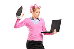 Woman with hair rollers holding an iron Royalty Free Stock Image