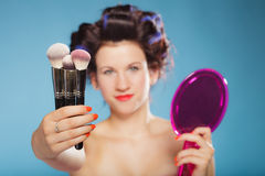 Woman in hair rollers holds makeup brushes Royalty Free Stock Image