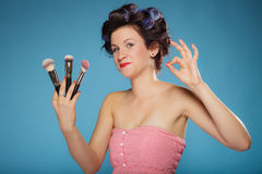 Woman in hair rollers holds makeup brushes Stock Photo