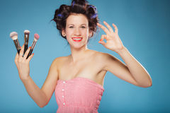 Woman in hair rollers holds makeup brushes Stock Photos