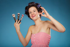 Woman in hair rollers holds makeup brushes Royalty Free Stock Photo