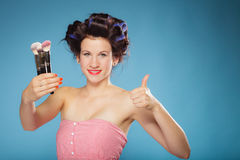 Woman in hair rollers holds makeup brushes Royalty Free Stock Photos